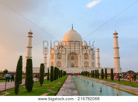Agra India - Jul 13 2015. Indian people visit Taj Mahal at sunset in Agra India. The palace was commissioned in 1632 by Shah Jahan to house the tomb of his favourite wife.