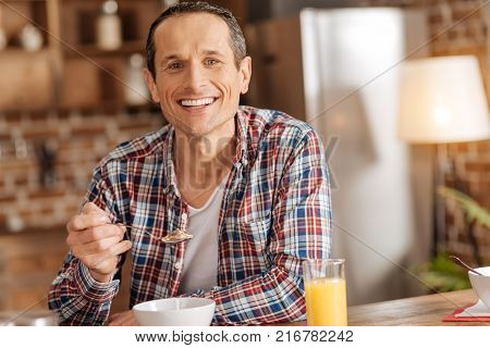 Enjoying food. Handsome upbeat man sitting at the kitchen table and eating cereals while posing for the camera and smiling