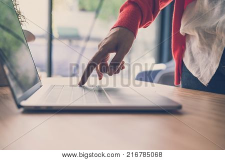 young start up woman wearing red cardigan press on computer at home. freelance female adult working with laptop at cafe. education, business concept.
