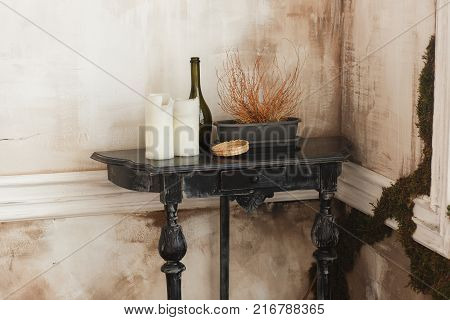 Old wooden black coffee table, candles, glass bottle flower pot in a corner of ancient room. Living interior and home decor concept.
