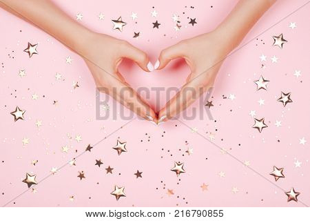 Beautiful young woman's hand with perfect manicure making heart on pink background. Flat lay style. Sparkles on background.