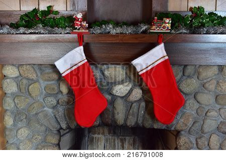 2 Christmas stockings hanging on stone fireplace with no names and not stuffed