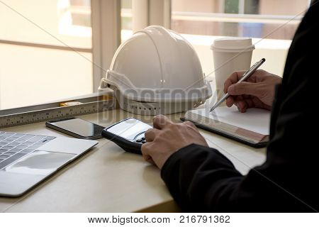 Close up of civil design engineer is making structural analysis calculations using a scientific calculator with laptop computer on the desk