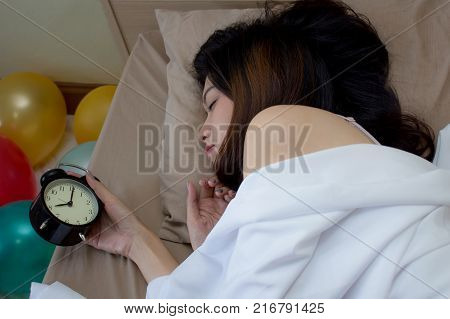 Asian girl on white bed wake up late hand turns off the alarm clock waking up at morning after drank too much booze last night.