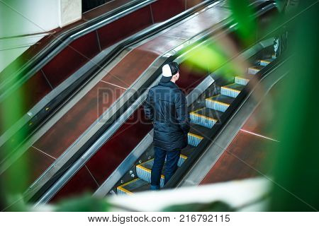 Back view man moving up on escalator in subway. Escalator in metro. Moving up staircase. electric escalator. View through the greenery. Selective soft focus