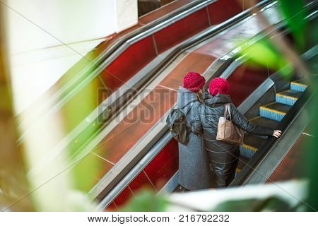 Back view two girls moving up on escalator in subway. Escalator in metro. Moving up staircase. electric escalator. View through the greenery. Selective soft focus
