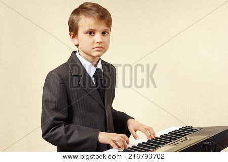 Young pianist in a suit playing the digital piano