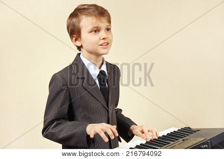 Young beginner musician in a suit playing the electronic piano