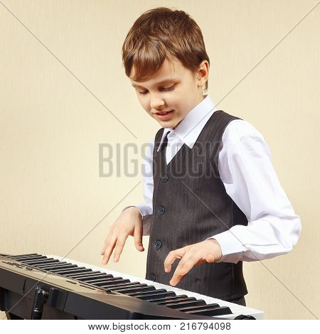 Little beginner pianist in a suit playing the digital piano
