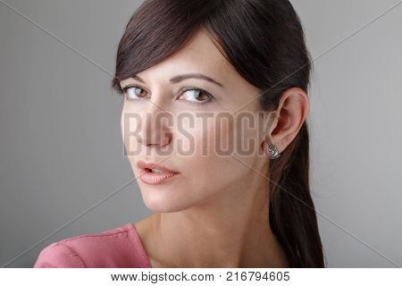 Closeup portrait of beautiful surprised young brunette Caucasian woman with brown eyes looking in camera. Girl female with long dark hair in pink shirt clothes. Studio beauty shot.