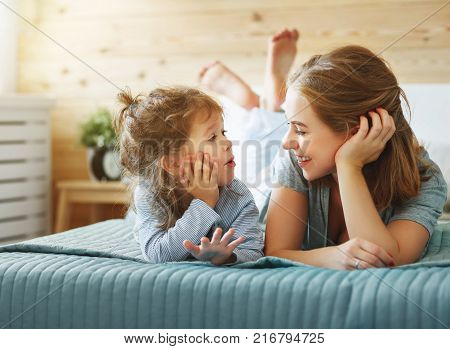 Happy family mother and child daughter play and laughing in bed