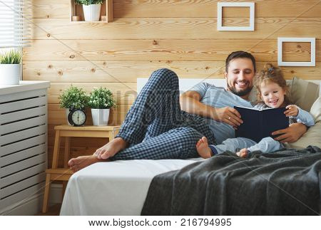 happy family father and child daughter reading book in bed
