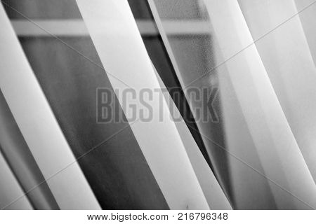 White background blinds folded. Delicate curtains on the window. Fabric curtained Windows.