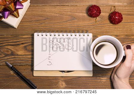 2018 goals inscription in a notebook, a pen, a hand holding a cup of black coffee and two red glitter balls. A rustic wooden Christmas or New Year background. Top view. Copy space