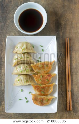 Eight boiled or fried jiaozi or gedza served with soy sauce. Selective focus.