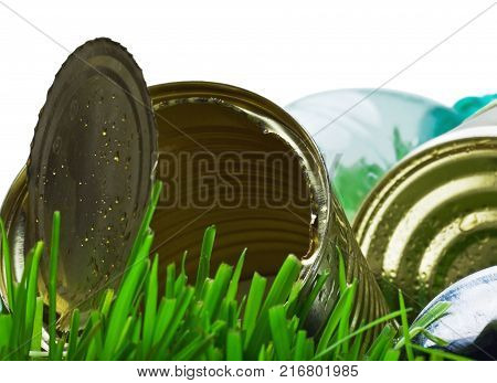 garbage from aluminum and tin cans on a green grass. Focus on the edges of the tin can