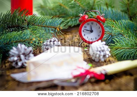 Clock alarm clock red cheese brie pine branches cones Cutlery fork knife on wooden background Concept of Christmas and New year On the clock 11:45 Selective focus Tinted