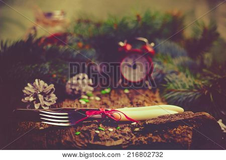 Red alarm clock on wooden background with green branches of pine cones and Cutlery On the clock 11:45 - it's eleven forty five Concept of the Christmas and New Year Selective focus Vintage tinted