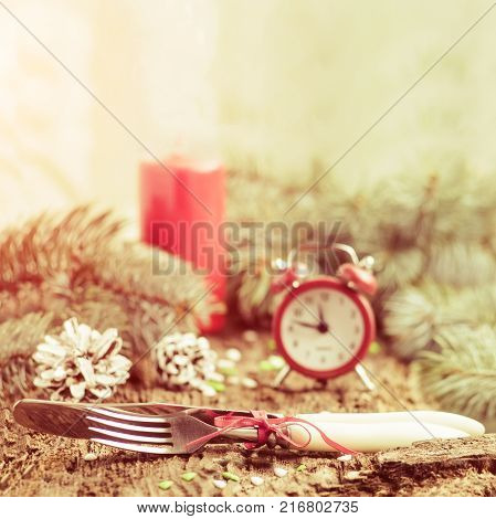Clock alarm clock red candle pine branches Cutlery fork knife on wooden background preparation for the celebration of Christmas and New year. Selective focus Vintage tinted