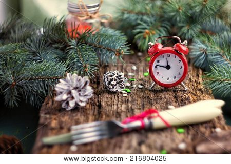 Red alarm clock on wooden background with green branches of pine cones and Cutlery. On the clock 11:45 - it's eleven forty five. The concept of the Christmas and New Year