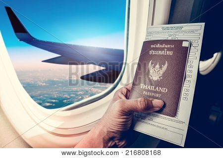 Business man holding passport and immigration form on seat next to windows on airplane vacation jorney. Hand holding passport with passport close up on plane windows background.
