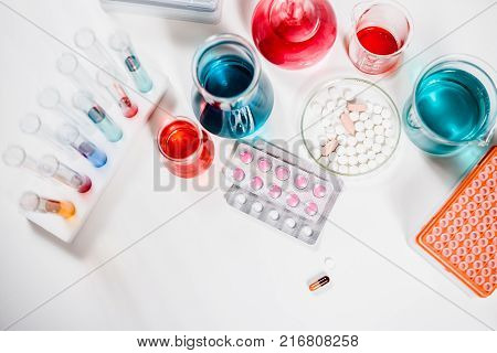 pills and test tubes in laboratory. drug discovery, pharmacology and biotechnology concept. science and medical research background.