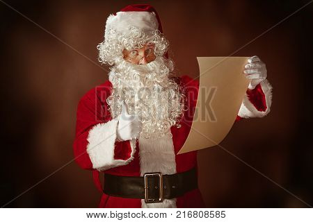 Portrait of Man in Santa Claus Costume - with a Luxurious White Beard, Santa's Hat and a Red Costume reading letter at red studio background with gifts