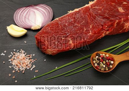One raw beefsteak red meat cut spices peppercorn in wooden scoop green spring chive onion garlic and Himalayan salt on black slate board close up high ange view
