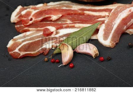 Raw pork bacon slices rashers spices rose peppercorns garlic and laurel bay leaves on black slate board close up high angle view