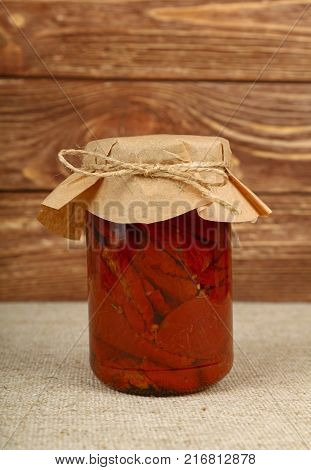Close up of one glass jar of pickled red sundried cured tomatoes in oil with kraft paper top decoration and twine on canvas tablecloth over brown wooden background low angle side view