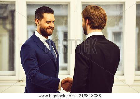 Boss and employee shaking hands to seal deal with his partner. Job placement concept