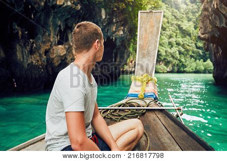 Young man tourist on the traditional long tail boat against lagoon. Ko Hong Island between Phuket and Krabi in Thailand.