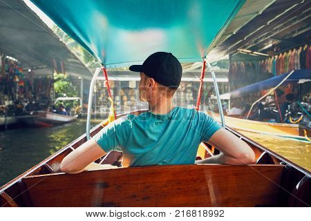 Young man traveler  on the boat. Traditional floating market Damnoen Saduak in Ratchaburi near Bangkok Thailand.