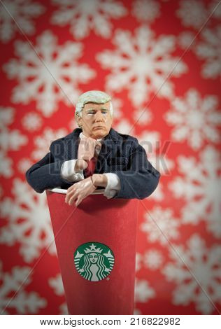 Donald Trump caricature action figure coming out of a Starbucks coffee cup. Trump has waged a Twitter war with Starbucks over their holiday cups