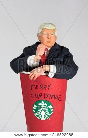 Donald Trump caricature action figure coming out of a Starbucks coffee cup with Merry Christmas written in child like text. Trump has waged a Twitter war with Starbucks over their holiday cups