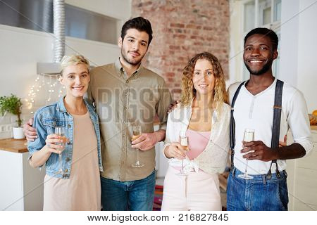 Two young affectionate couple holding flutes with champagne while gathering at home