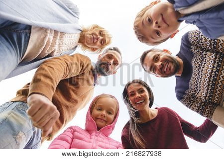 Bottom view of a big positive family standing outdoors and looking at camera