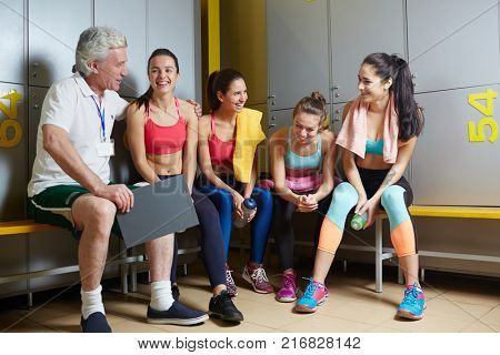 Mature trainer encouraging his female sports team for greater results and achievement during workouts