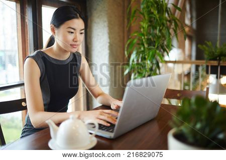 Asian businesswoman typing on laptop while sitting by table in modern office or cafe