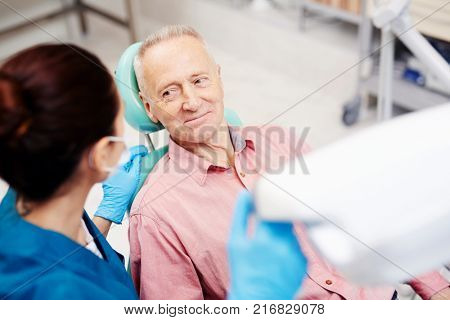 Senior man looking at his dentist and listening to her advice after oral check-up