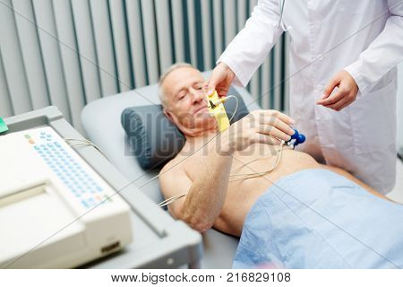 Cardiologist going to examine senior man heartbeat and pulse in hospital