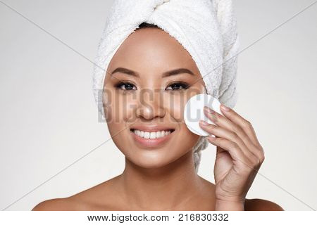 Smiling attractive half-naked asian lady with towel on head cleaning her face with cotton pad and smiling isolated over grey