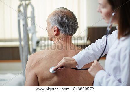 Modern practitioner examining mature man lungs and breath with stethoscope