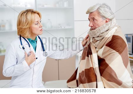 Mid-aged therapeutist supporting her sick patient wrapped into plaid