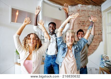 Group of young companions raising their hands while dancing at leisure