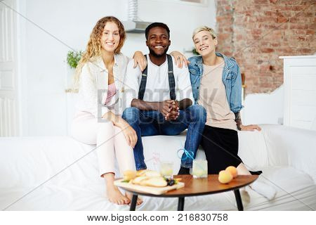 Three intercultural friends sitting on white comfortable sofa while spending time together
