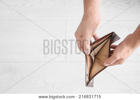 Hands of young man with empty purse on light background