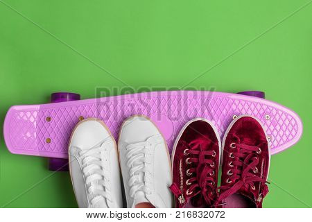 Female sport shoes with skateboard on color background