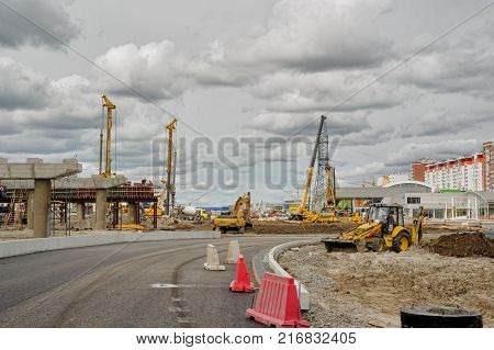 Tyumen, Russia - June 1, 2017: JSC Mostostroy-11. Construction of two-level outcome on bypass road on Fedyuninskogo and Permyakova streets intersection. Construction equipment in action