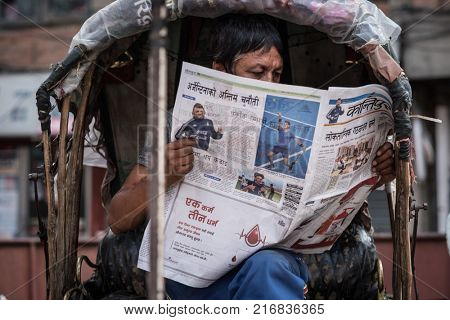 Kathmandu, Nepal - 06 October 2017: Middle-aged man sits in old rickshaw cabin and reads newspaper.